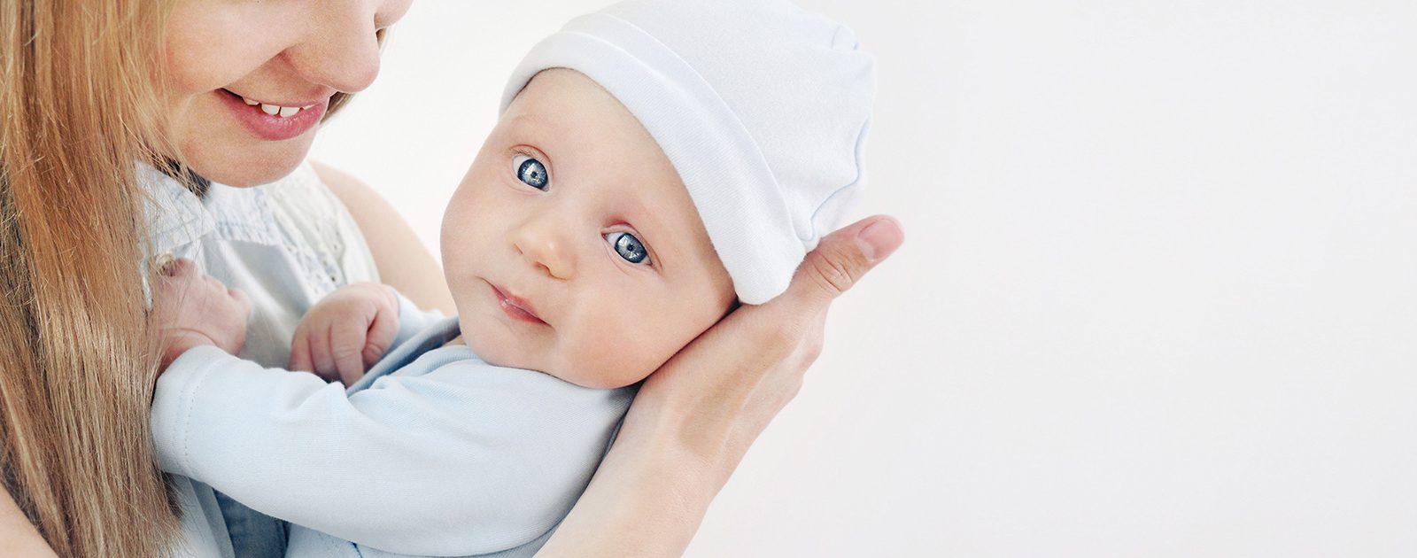 Frau mit adoptiertem Baby: mit einer (offenen) Adoption Kinderwunsch erfüllen