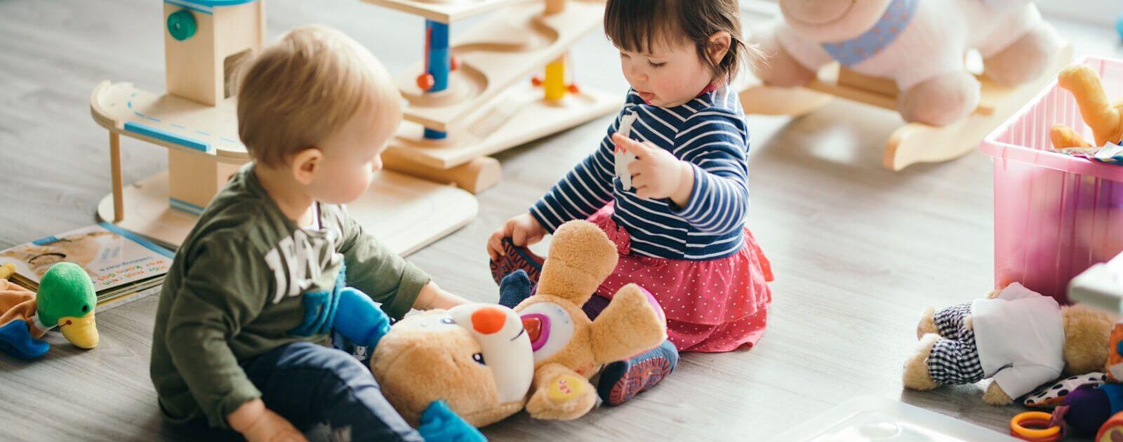 Entwicklung von Kindern: Zwei Kleinkinder spielen gemeinsam mit einem Teddybär.