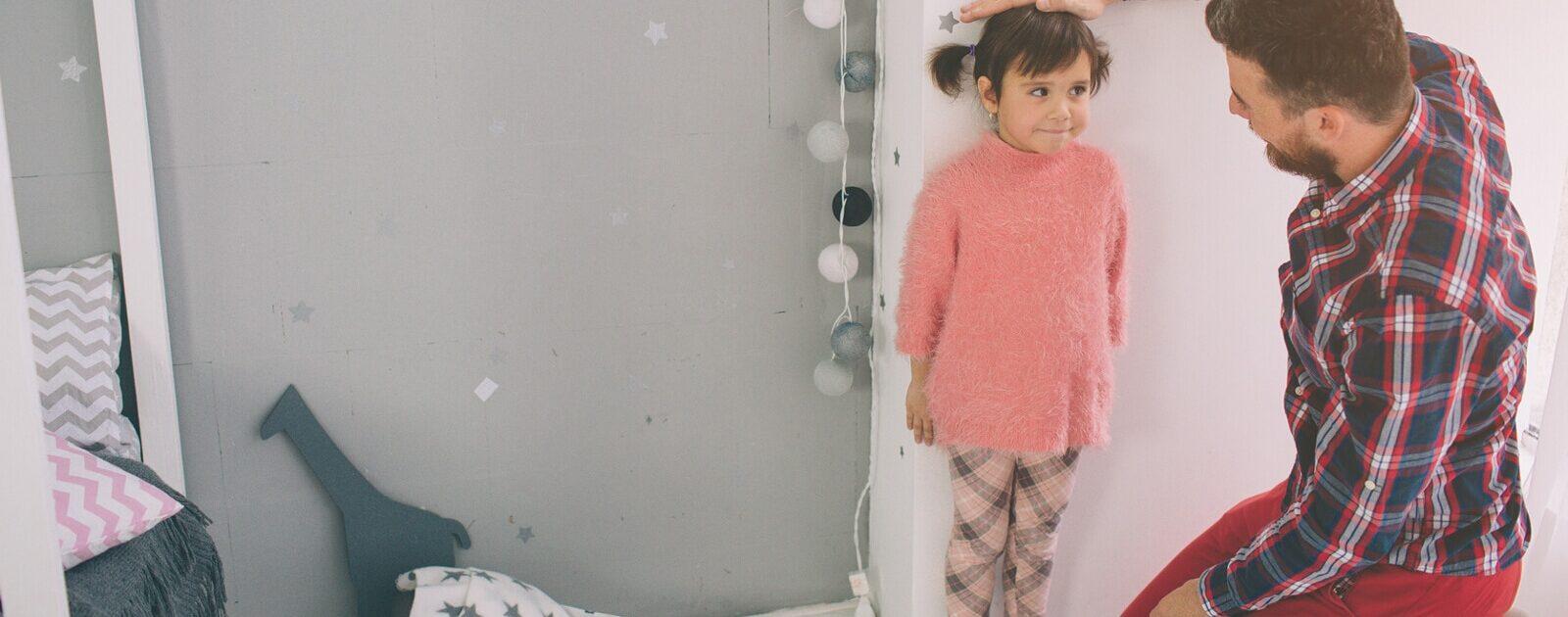 Ein Vater misst die Körpergröße seiner kleinen Tochter.