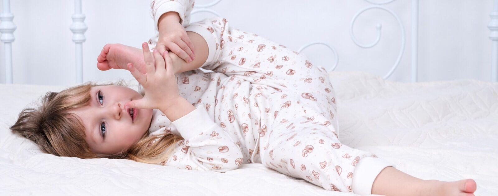 Die körperliche Entwicklung von Kleinkindern: Ein Mädchen zieht den Fuß zu ihrem Gesicht.