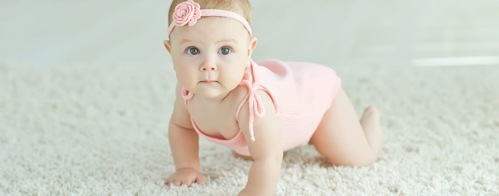 Symbolbild Motorik: Baby krabbelt über den Boden.
