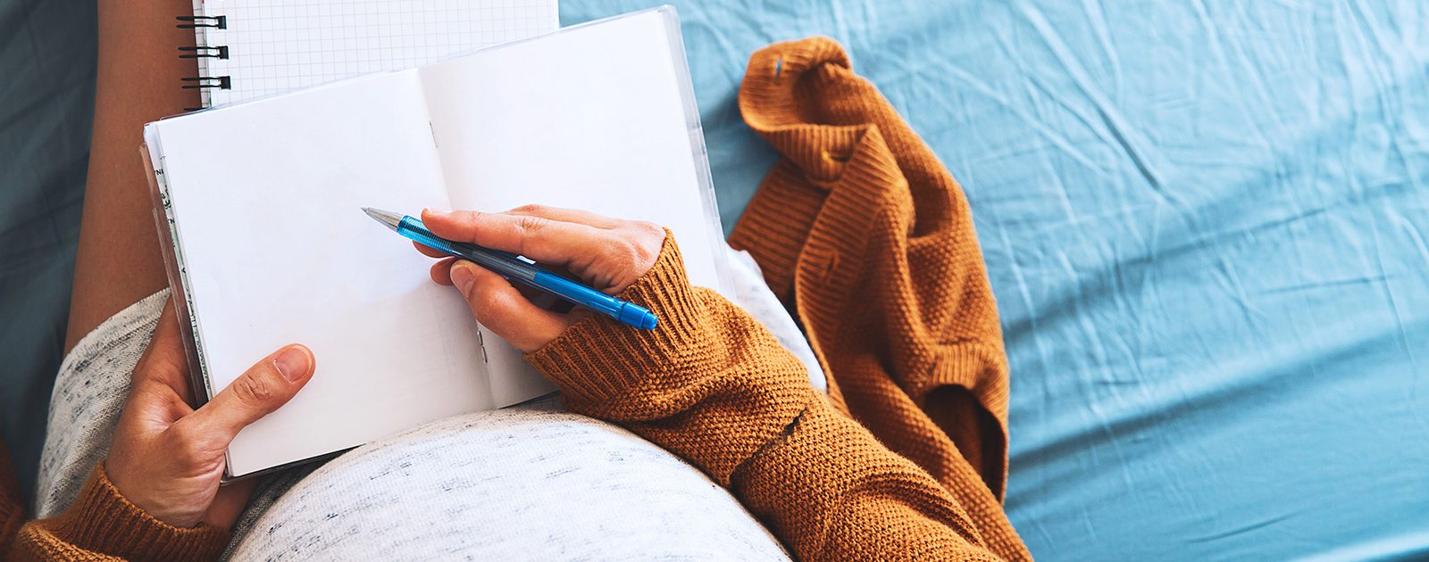 Schwangere Frau erstellt mit dem Laptop eine Checkliste für die Schwangerschaft und Geburt