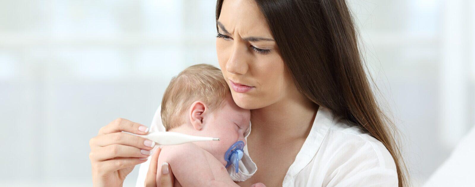 Dreitagefieber: Eine besorgte Mutter misst das Fieber ihres Babys.