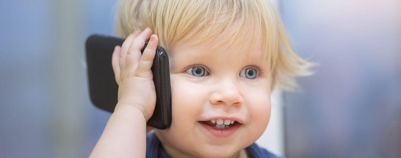 Die ersten Worte: Ein Baby spricht in ein Telefon