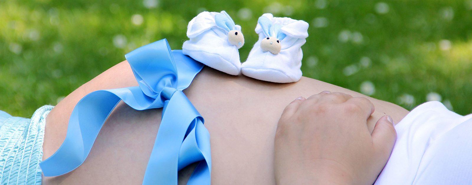 Geburtsvorbereitung Babyausstattung: Babyschuhe auf Schwangerschaftsbauch