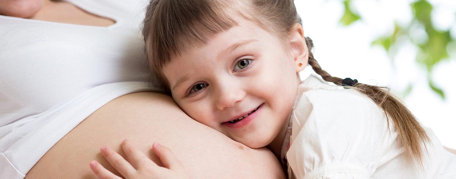 Kind liegt auf dem Schwangerschaftsbauch der Mutter: Teilnahme an der Schwangerschaft der Mutter beugt Eifersucht unter Geschwistern vor