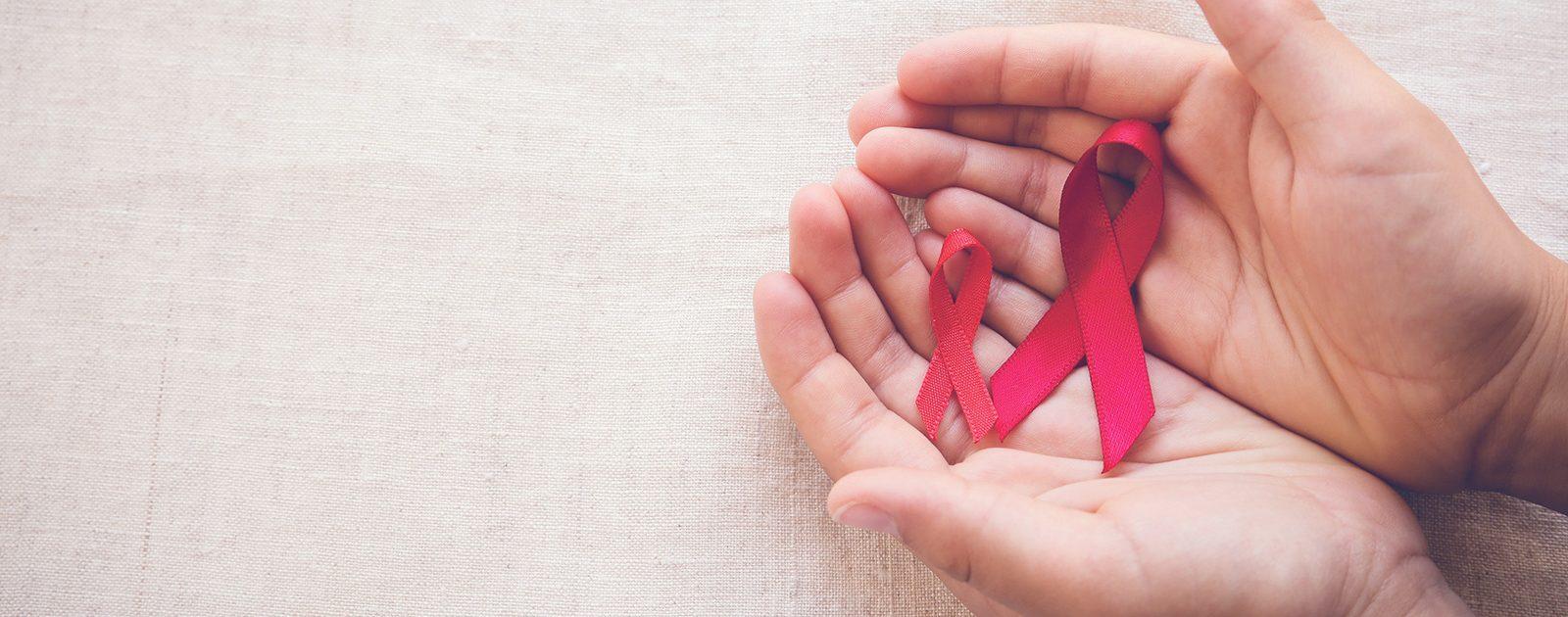 Aids-Schleifen in Hand: Ist eine Schwangerschaft trotz HIV möglich?