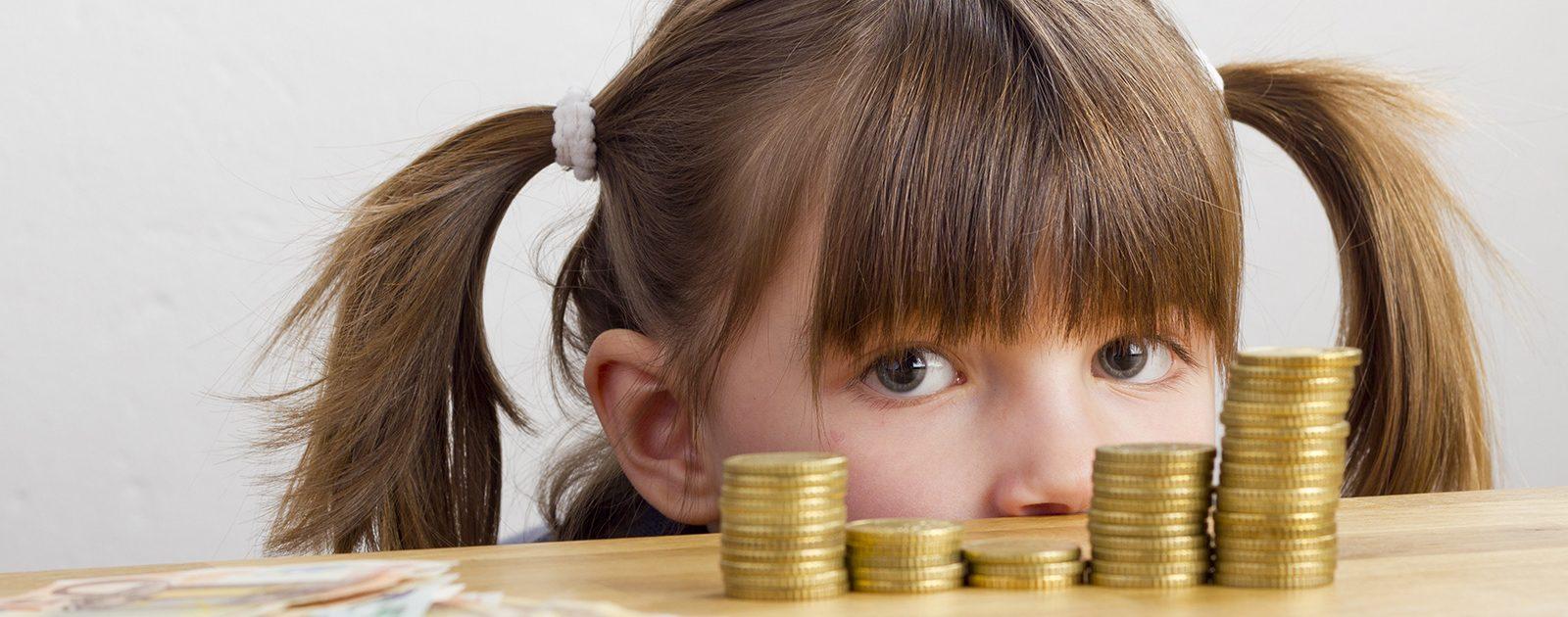 Kind vor einem gesparten Stapel Kindergeld: Dauer der Förderung