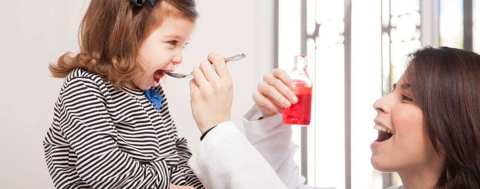 Ein Mädchen erhält von einer Ärztin ein Medikament.