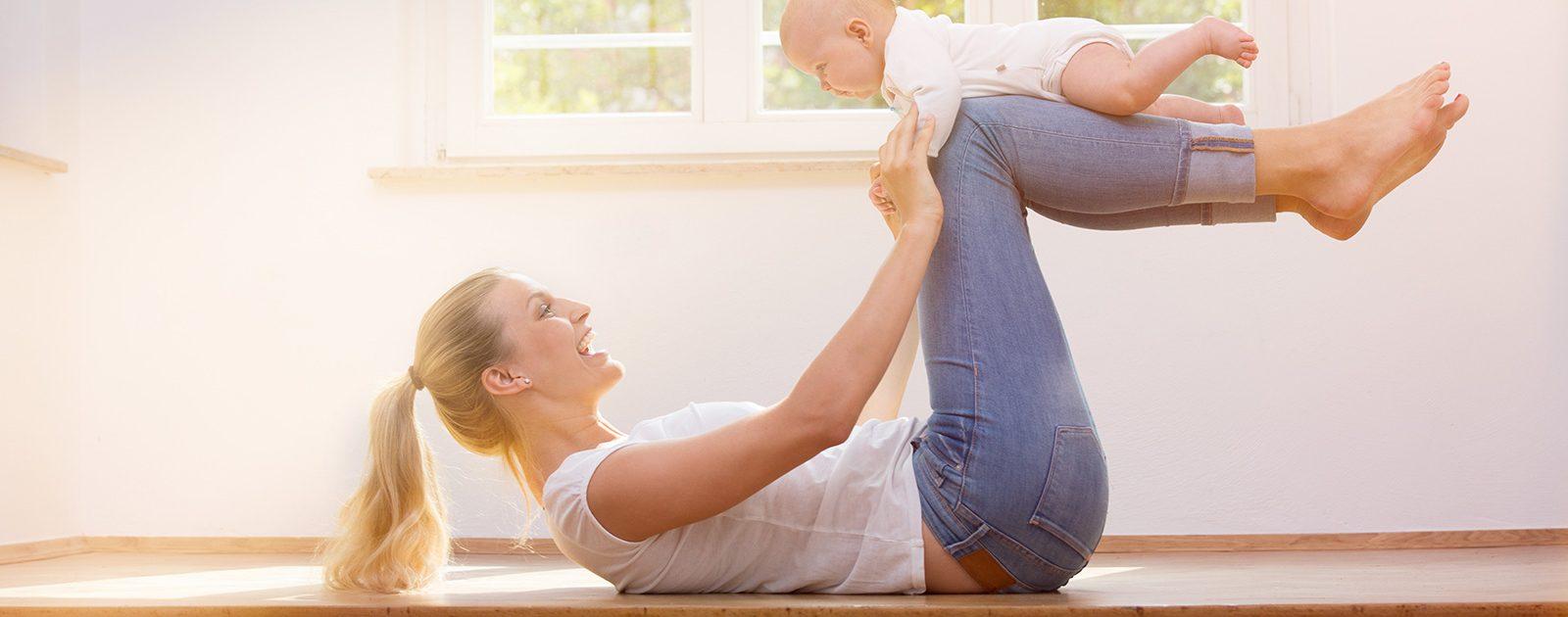 Mutter mit Baby bei Übungen zur Rückbildung