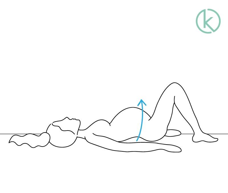 Schwangere mit Rückenschmerzen macht Übung zur Kräftigung ihres Rückens.