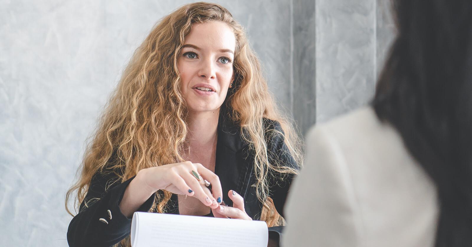 Frau teilt im vertraulichen Gespräch ihrer Chefin ihre Schwangerschaft mit.