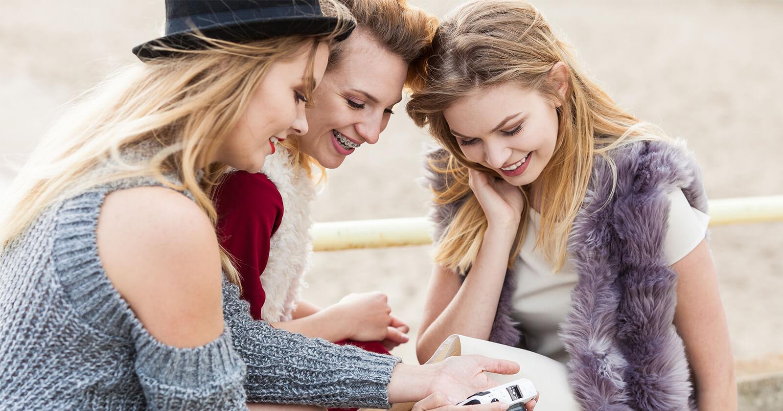 Frau zeigt Freundinnen Fotos auf ihrer Kamera und verkündet mit einem Ultraschallbild ihre Schwangerschaft.