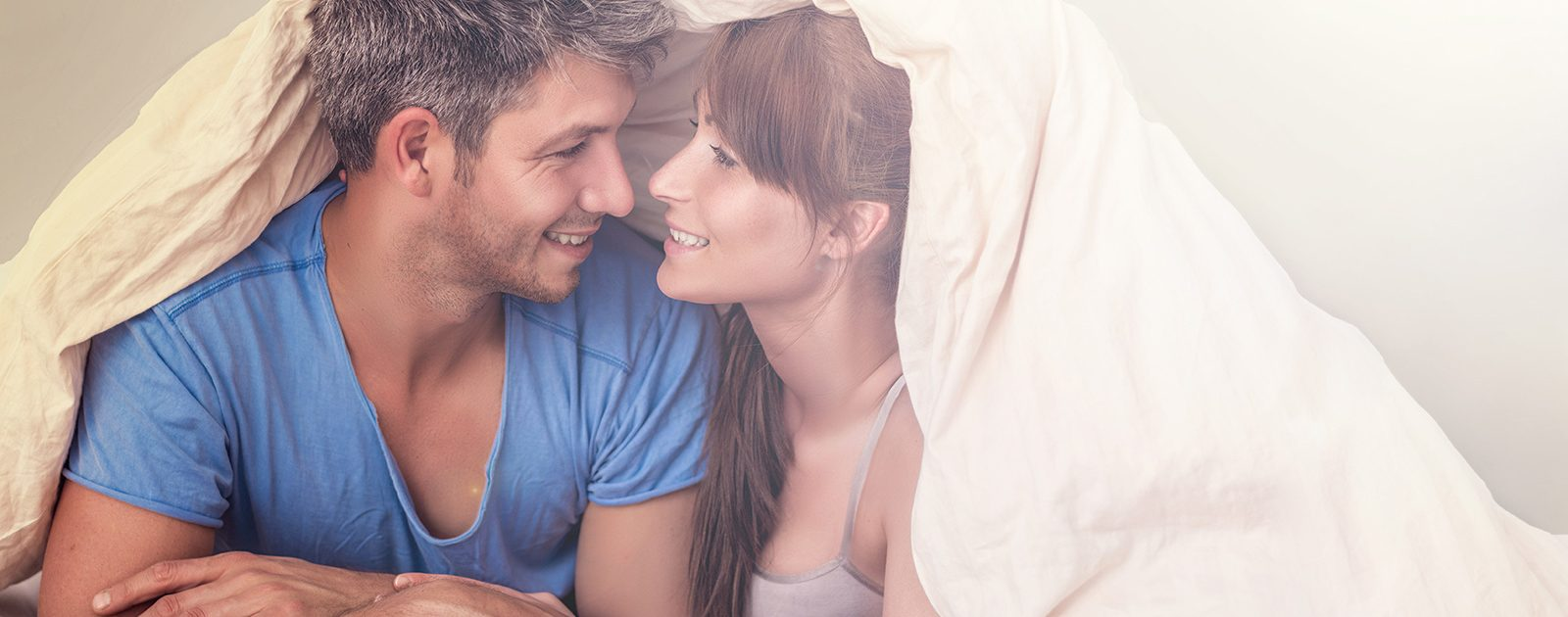 Frau und Mann unter der Bettdecke: Sex in der Schwangerschaft