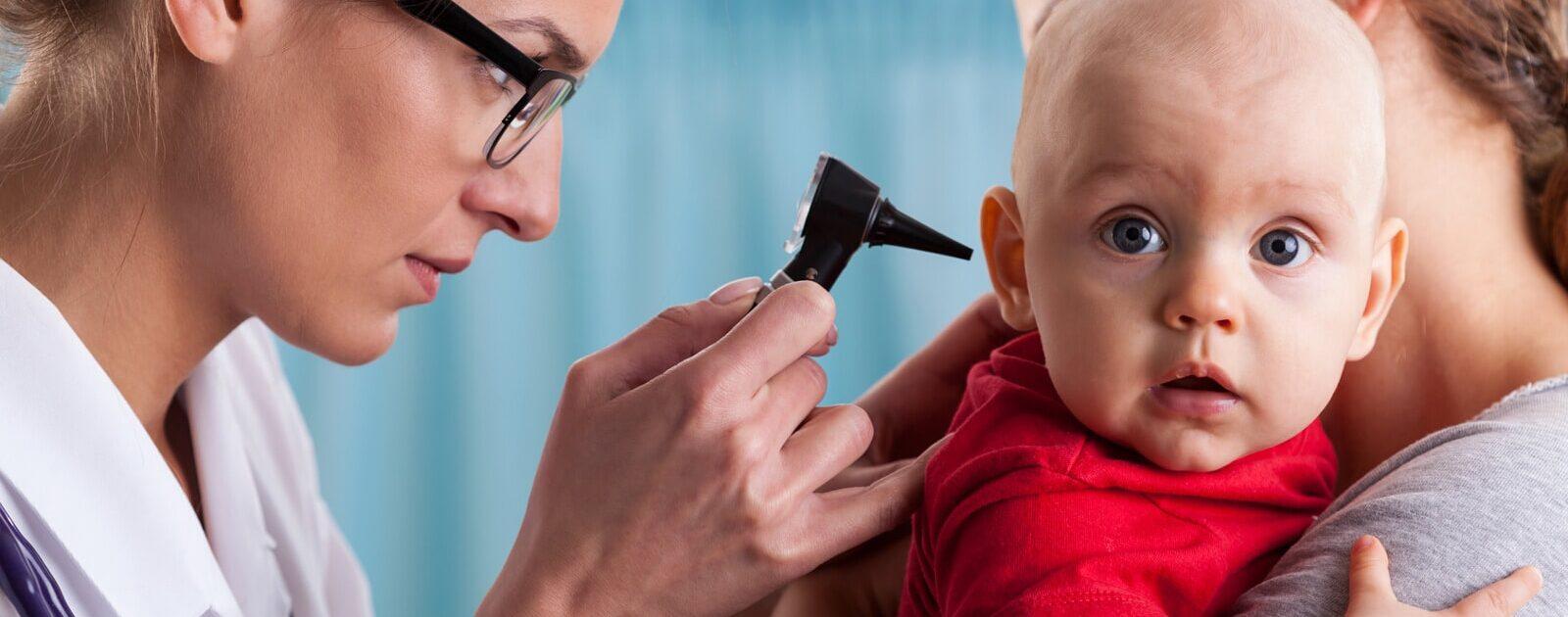 Ein Arzt schaut in das Ohr eines Babys: Ohrenschmerzen gehören zu den typischen Babykrankheiten.