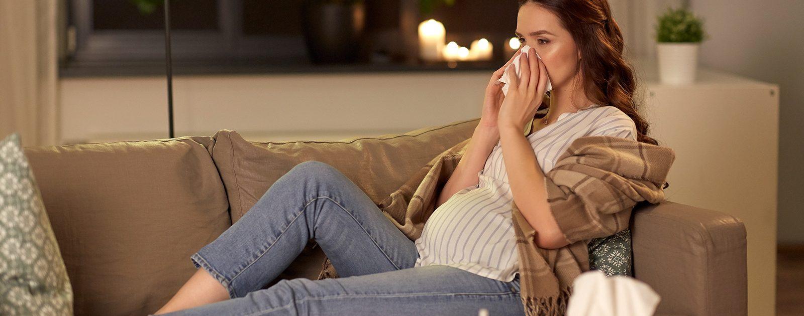 Schwangere Frau leidet an einer Schwangerschaftsrhinitis und muss sich die Nase putzen.