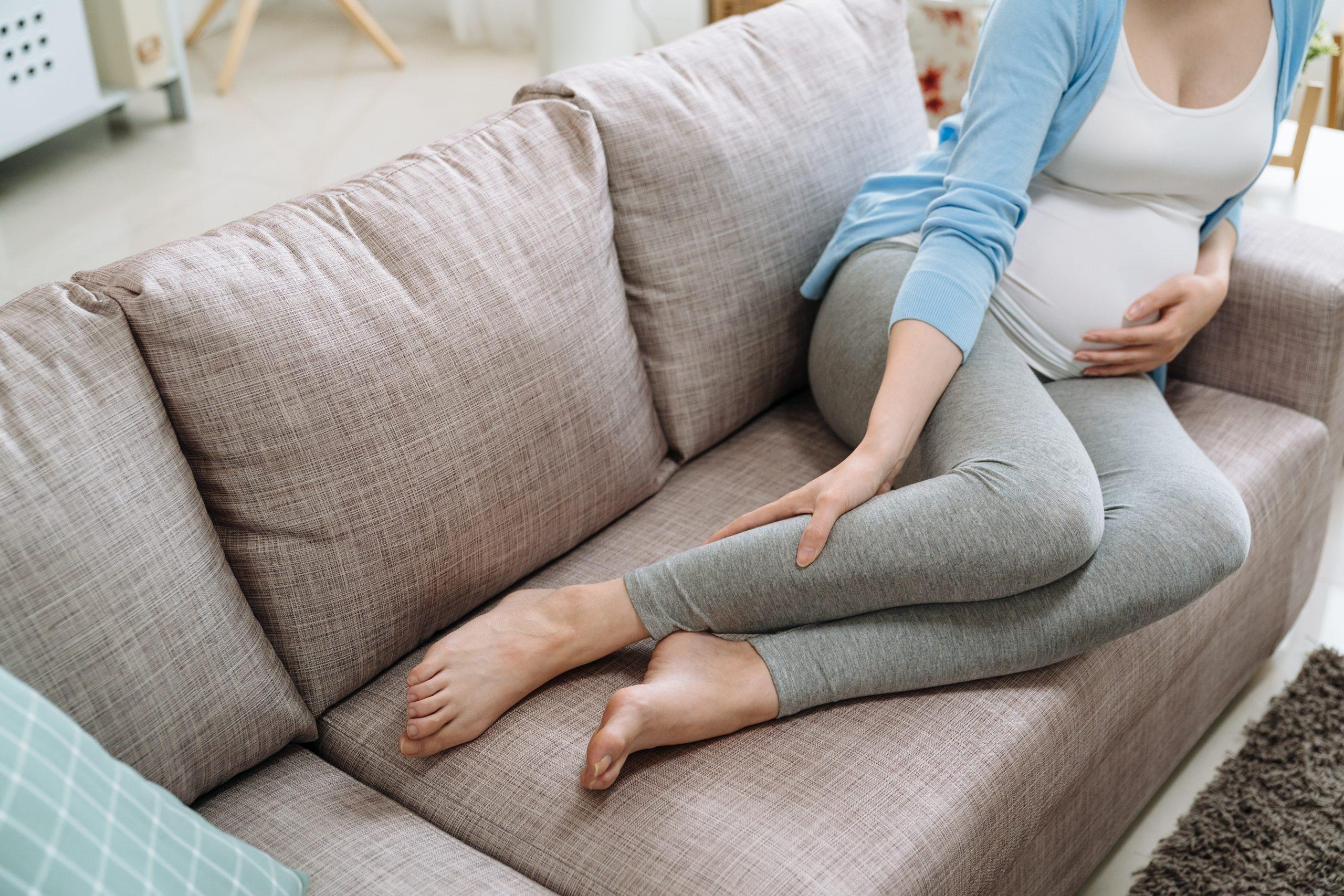 Schwangere Frau mit geschwollenen Beinen: Kompressionsstrümpfe können helfen.