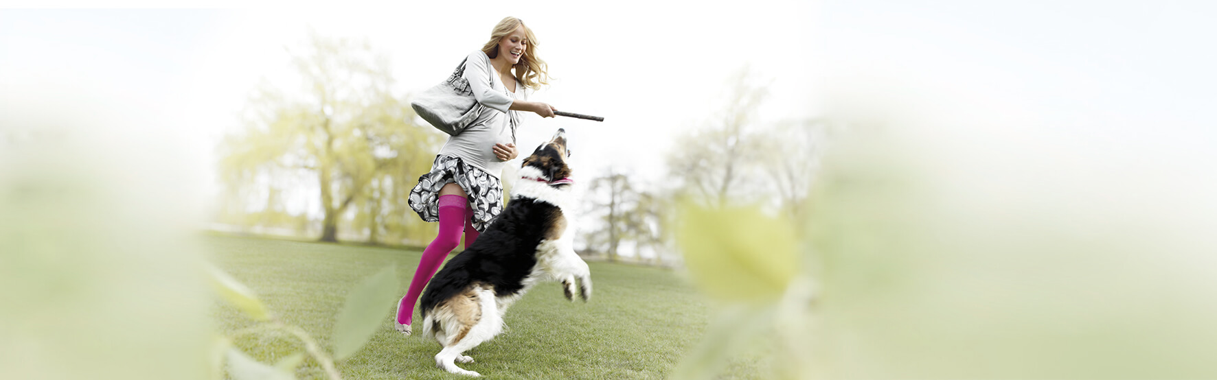 Schwangere Frau spielt mit Hund – mit den mediven Kompressionsstrümpfen konnte sie ihre Ödeme reduzieren.