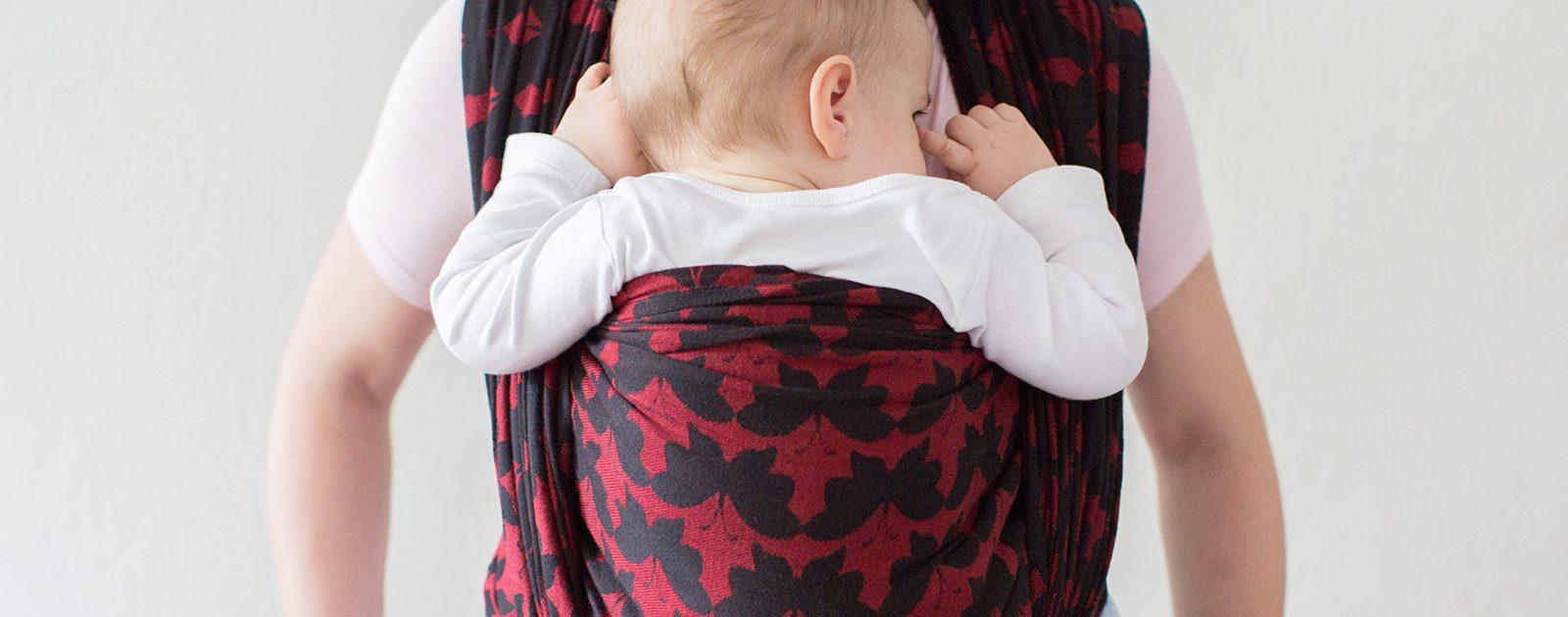 Eine Mutter trägt ihr Baby in einem Tragetuch.
