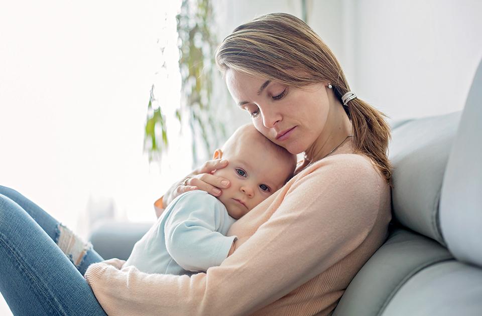 Eine Mutter tröstet ihr Baby, weil es aufgrund eines geschwächten Immunsystems krank ist.