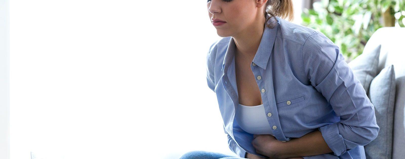 Schwangere krümmt sich – bei ihr wird der Durchfall in der Schwangerschaft von Bauchschmerzen begleitet.