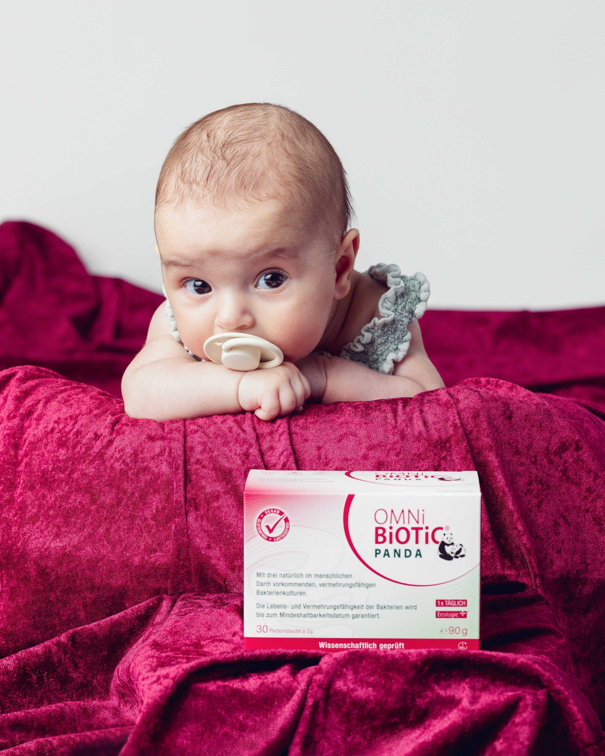 Baby liegt auf rotem Tuch mit OMNi-BiOTiC® PANDA im Vordergrund.